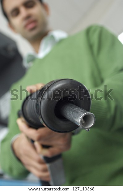 Low angle view of man holding petrol nozzle