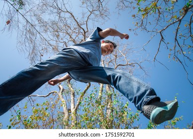 Low angle view of man midair by jumping, crossing step over the camera shot below in forest with tree and sky overhead in concept travel, active lifestyle, overcome obstacles in life or future