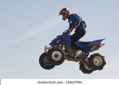 Low angle view of a man riding quad bike in midair against the blue sky