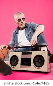 low angle view of man in sunglasses sitting near tape recorder and basketball ball isolated on pink