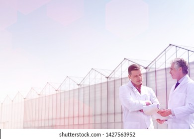 Low angle view of mature male biochemists discussing while standing against clear blue sky
