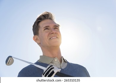 Low angle view of mature man holding golf club against sky