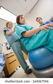 Low angle view mature nurse assisting pregnant woman sitting on exercise ball while man looking at her in hospital