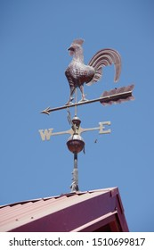 Low angle view of a metal weathervane in the form of a rooster high on a roof under a bright blue sky