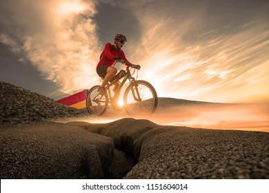 Low angle view mountain bike cyclist cycling on the hill mountain twilight time on top of a mountain , Extreme sport concept.