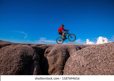 Low angle view mountain bike cyclist cycling on the hill mountain with clear sky on top of a mountain . Extreme sport concept.