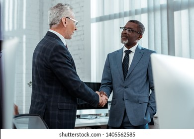 low angle view of multicultural businessmen shaking hands in office