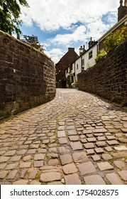 A low angle view of narrow cobbled ally way with tall sandstone walls leading lines Victorian gas lighting old town housing.