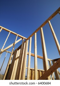 Low angle view of new construction framework for house with blue sky.
