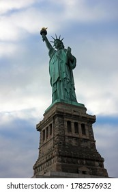 Low angle view of New Yorks Statue Of Liberty with grey dark clouds in background upcoming bad weather