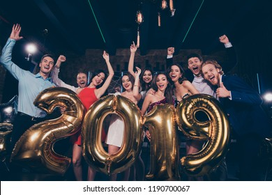 Low angle view of nice beautiful adorable pretty glamorous charming cheerful glad funny ladies and handsome gentlemen, cocktail party, chill out at night club, holding 2019 golden symbol figure