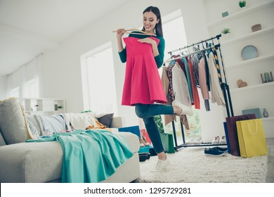 Low angle view of nice-looking lovely attractive pretty charming cheerful funny cheery positive girl lady holding trying on new dress preparing for event in light white interior room
