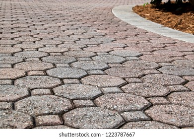Low angle view of octagon and square shaped brick pavers with curved section of driveway with rectangle bricks along edge. Shows mulch and curves to right.