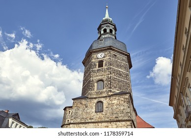 low angle view of old historical church of St John with clock against blue sky in Bad Schandau, Germany