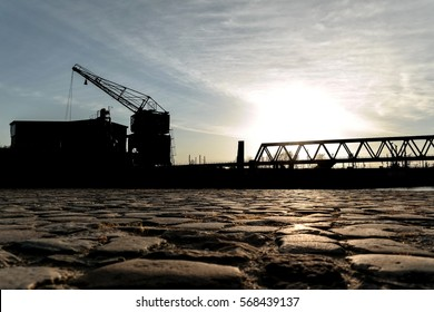 low angle view of old industrial crane silhouette at sunset