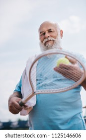 low angle view of old man with towel and tennis equipment in hands