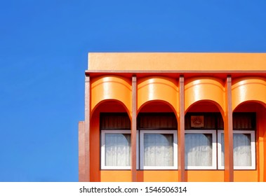 Low angle view of the old vintage colorful orange facade with arched balcony and white windows in colonnade style against blue clear sky background