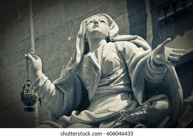 Low angle view on beautiful stone sculpture of pious woman holding lamp outside in Europe