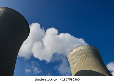 Low angle view on cooling towers with water steam on a blue sky, nuclear plant