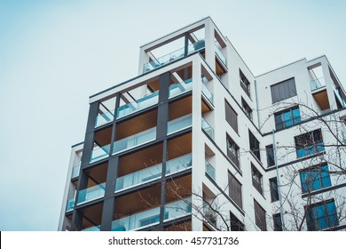 Low angle view on exterior of urban apartment building balconies with glass barrier