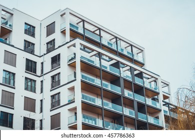 Low angle view on modern high-rise flats with open roof balconies under overcast gray sky