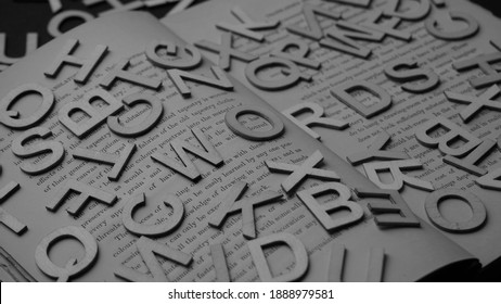 Low angle view on opened book with English printed text. Word of 3d letters. ABC. Scattered letters. Literature. Education. Monochrome. White black photo. - 26 December 2020, Montreal, Canada