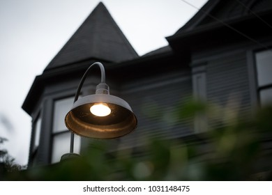 Low angle view on a round street lamp outside of a dark haunted house, with a pointed spire top roof