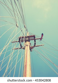Low angle view on a sailing boat wooden mast on a sunny day, with clear blue sky in the background. Image filtered in faded, retro, Instagram style with soft focus; vintage concept of summer travel.