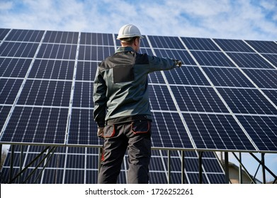 Low angle view on technician in dark blue uniform standing with his back to the camera, pointing at solar plant. Rear view. Alternative ecological source of energy concept