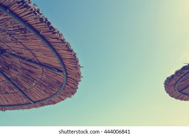 Low angle view on two straw parasols on the beach, on a sunny day, with blue sky in the middle. Can be used as summer background. Image filtered in faded, retro, Instagram style with soft focus.
