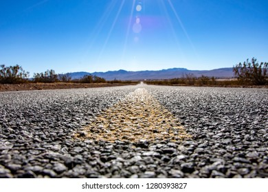 Low angle view of open road stretching straight to horizon with mountains in distance