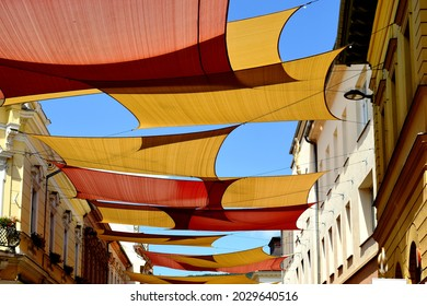Low angle view of patio awning. colorful tightly weaved sun sail UV protection fabric suspended from exterior walls. urban street in old city downtown area. sun protection. summer holiday concept.