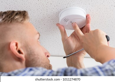 Low Angle View Of A Person's Hand Installing Smoke Detector On Ceiling Wall At Home