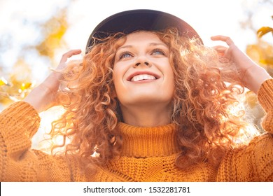 Low angle view portrait of charming ginger young adult women wearing in knitter orange sweater and hat looking up. Beautiful cheerful lady standing outdoor and smiling wide