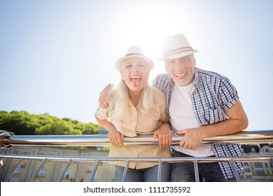 Low angle view portrait of comic cool grandma and granddad lean on balcony railing gesturing tongue out enjoying good weather sunny day crazy mood. Leisure rest relax concept