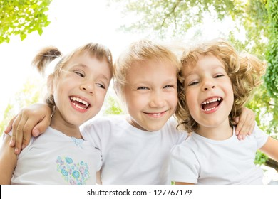 Low angle view portrait of happy children laughing outdoors in spring park