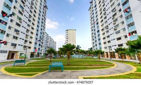 Low angle view of public housing HDB resident buildings/ flats complex with grass courtyard, trees and dense of apartments during sunset in Singapore. Urban concept. Panorama style.