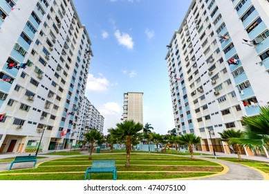Low angle view of public housing HDB resident buildings/ flats complex with grass courtyard, trees and dense of apartments during sunset in Singapore. Urban concept.
