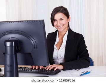 Low angle view of a relaxed smiling beautiful businesswoman sitting behind her desk working at her computer