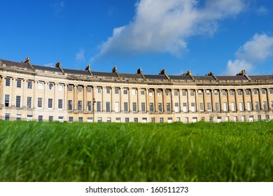 Low angle view of the Royal Crescent in Bath, Somerset with lush green lawn in the foreground.