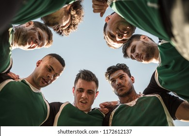 Low angle view of rugby players in circle against clear sky discussing their tactics. Team of rugby player in huddle between the match.