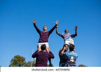 Low angle view of rugby players against clear sky on sunny day