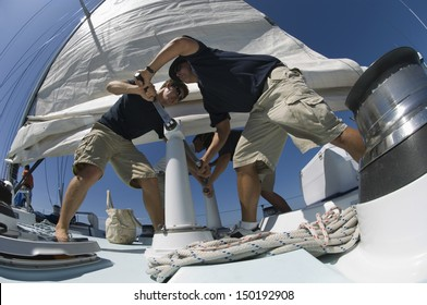 Low angle view of sailors operating windlass on yacht