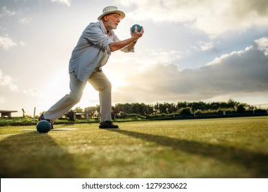 Low angle view of a senior man in position to throw a boule. Old man playing boules in a lawn with sun in the background.