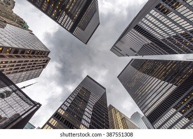 A low angle view of skyscrapers on an grey overcast day.