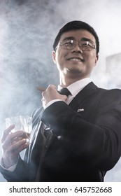 Low angle view of smiling asian man in eyeglasses drinking whiskey and smoking cigar