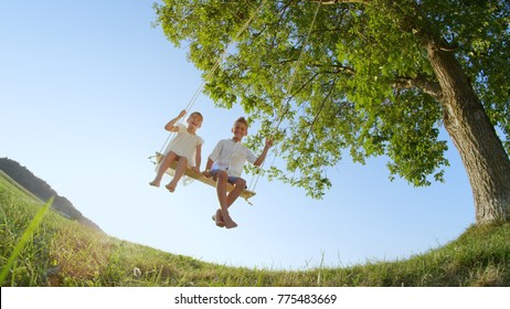 LOW ANGLE VIEW Smiling boy and girl enjoying a warm sunny day swinging under a big tree. Brother and sister having fun on outdoors swing set. Barefoot happy kids swaying on a swing hanging from a tree