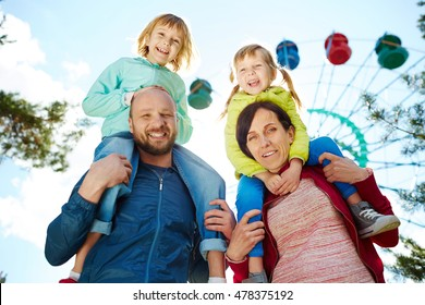 Low angle view of smiling family in amusement park, mother and father carrying their two adorable blond girls on shoulders and looking at camera during warm autumn weekend, ferris wheel in background