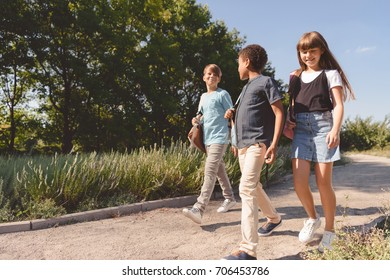 low angle view of smiling multiethnic teenagers with backpacks walking in park
