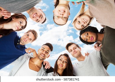 Low Angle View Of A Smiling Students Forming Huddle Against Sky